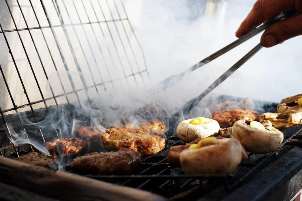 A cook using tongs on a gas grill.