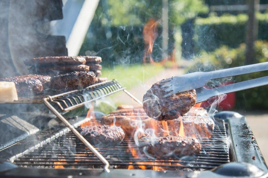 A smoking hot barbecue with burgers on the grate.