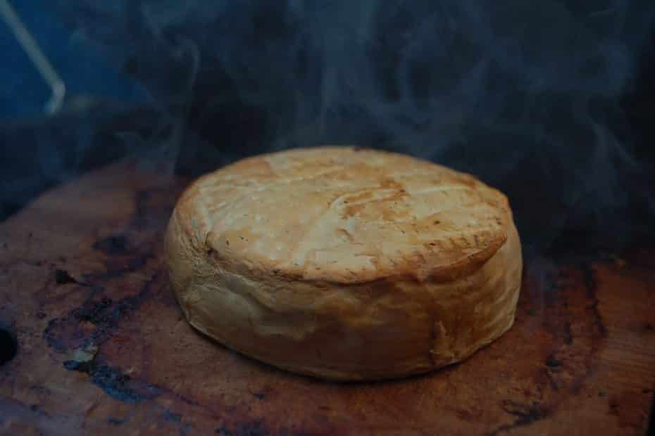 A large round piece of smoked cheese.