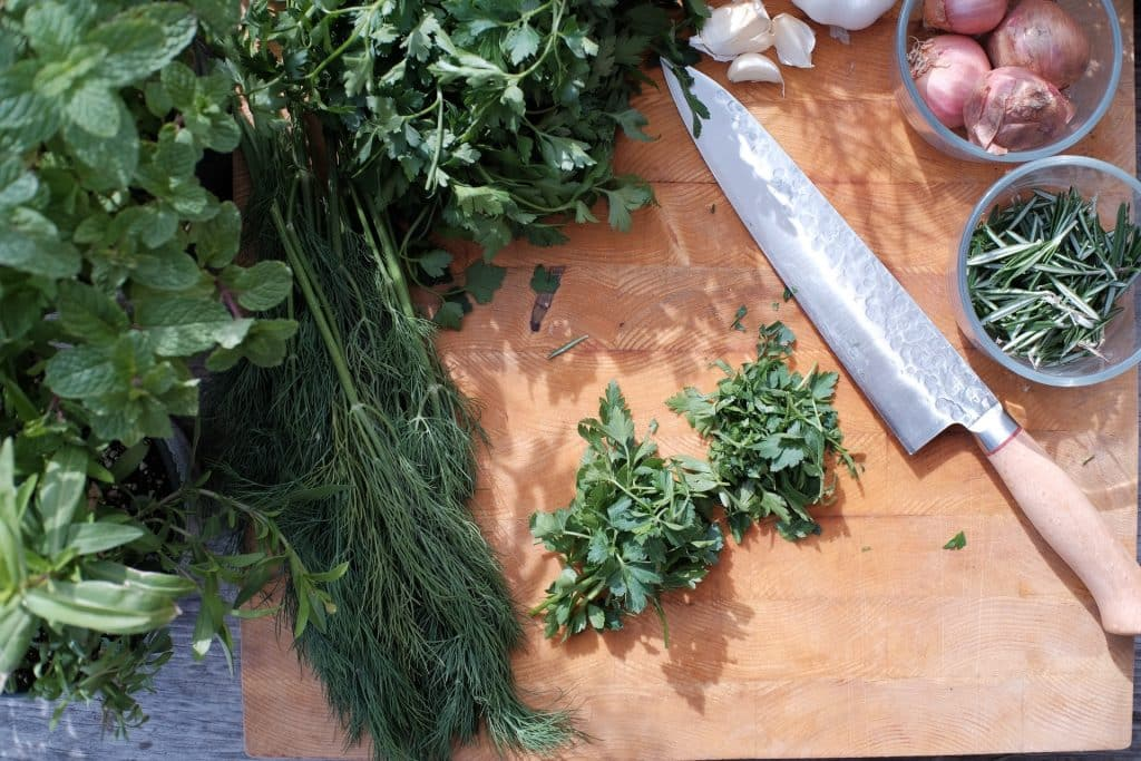 Fresh herbs on a cutting board with a knife.
