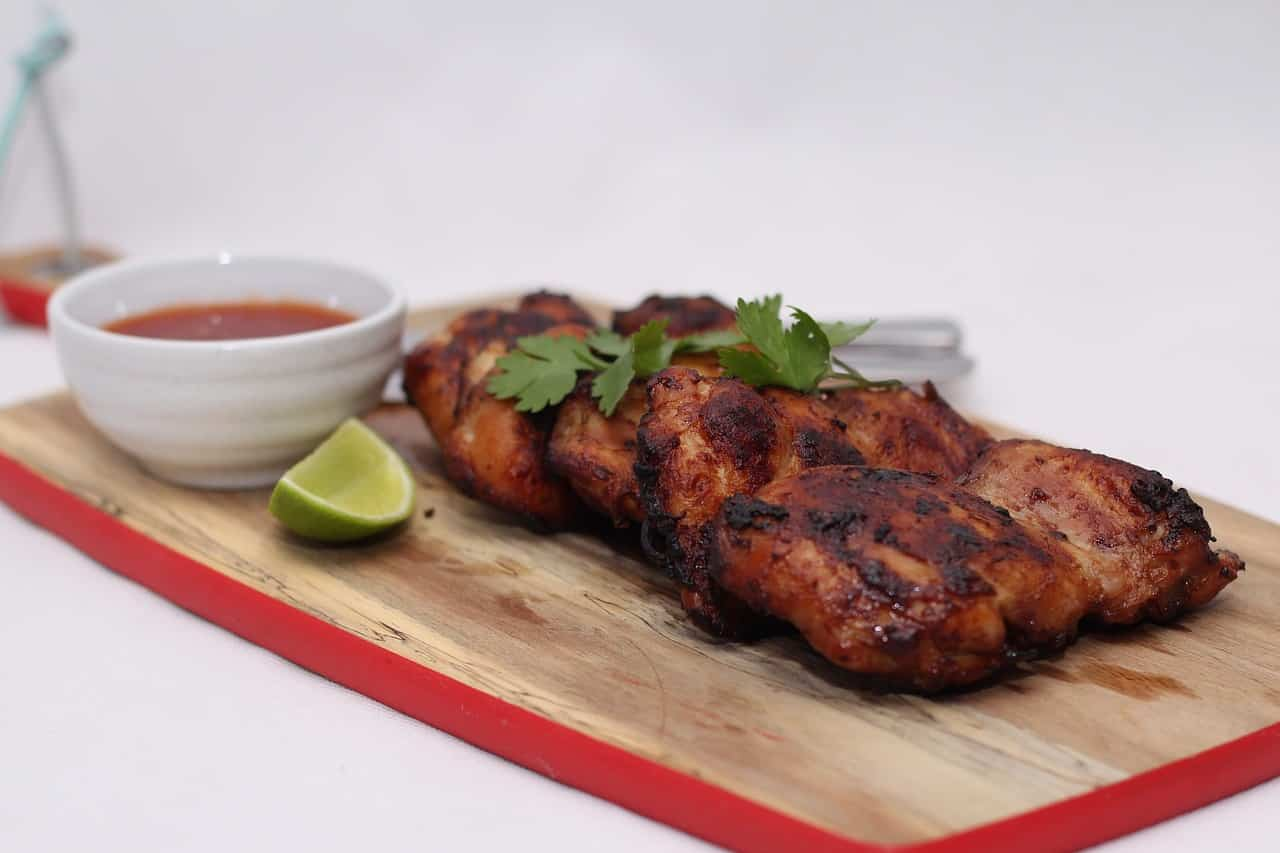Smoked chicken with a bowl of sauce and a lime slice on a cutting board.