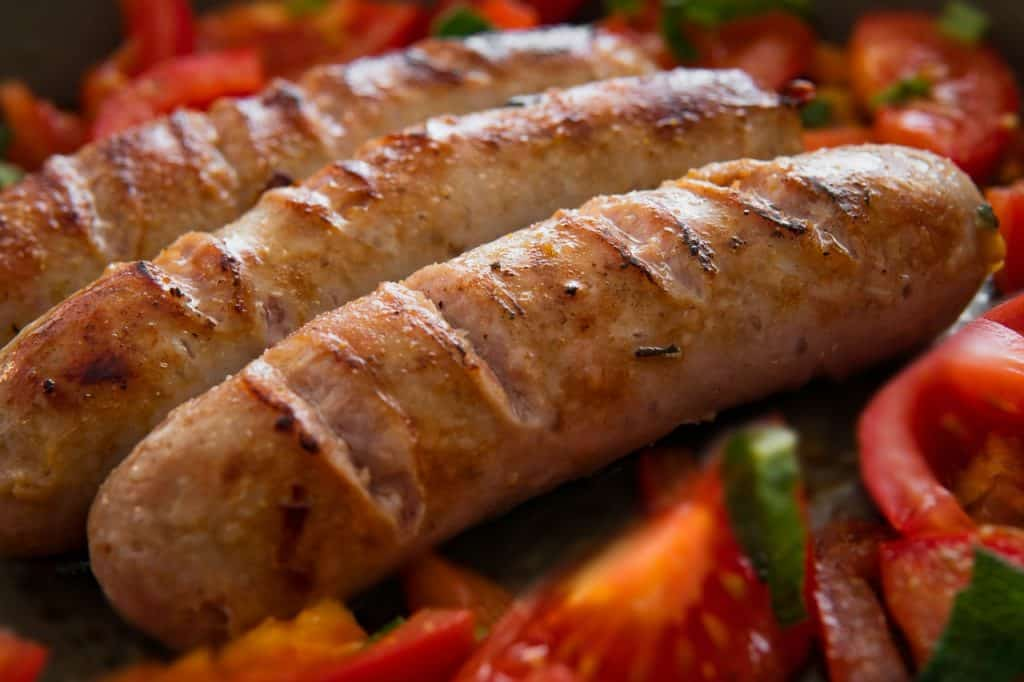 zoom-in of three grilled bratwursts on top of a base of vegetables