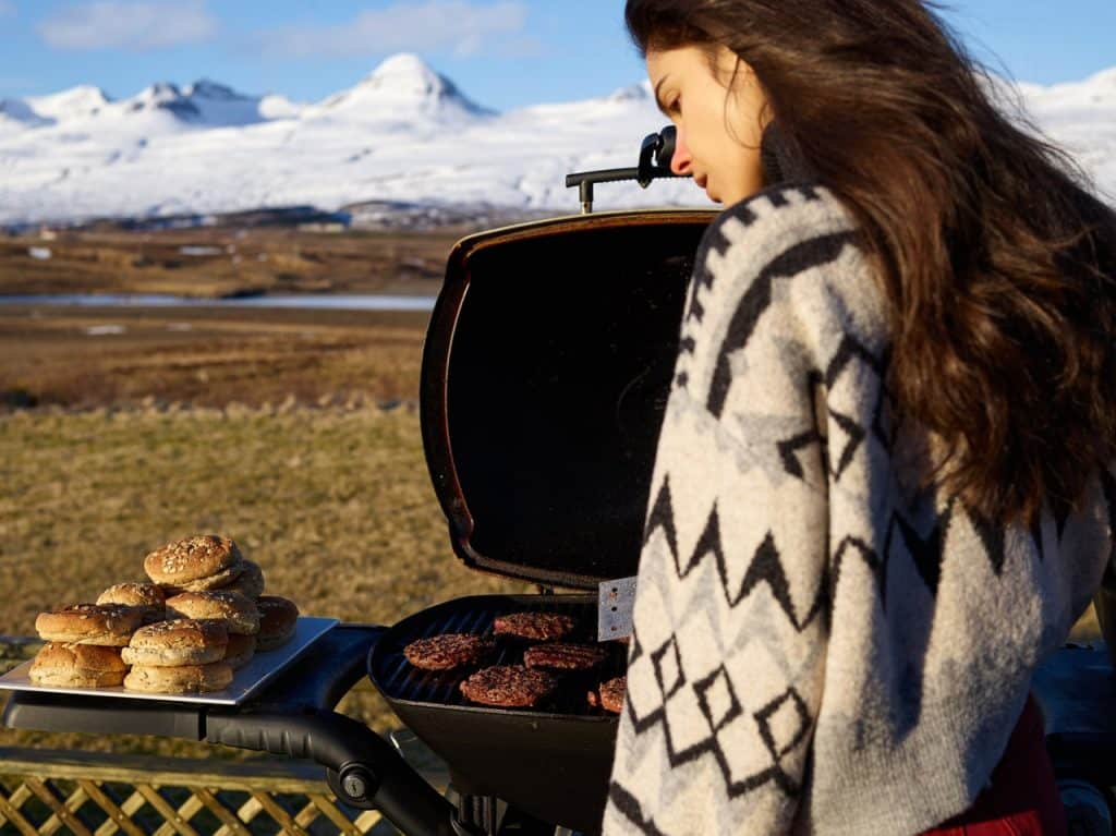 A woman grilling in front of snow-covered hills.