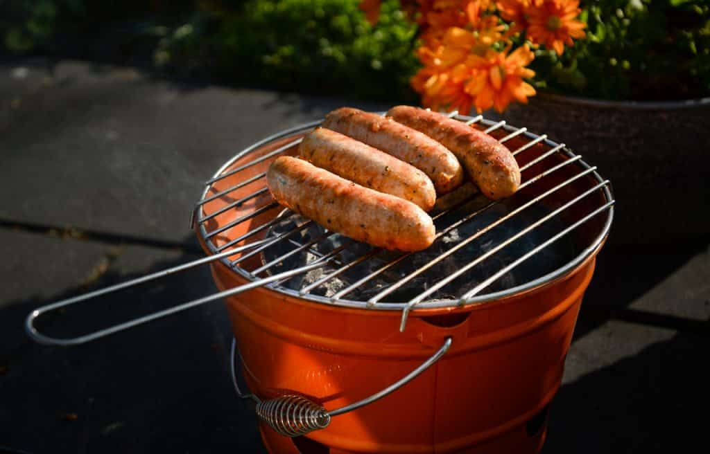 four bratwursts on an orange charcoal grill